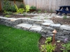 Dry stack wall with steps, new sod, patio, and landscape lighting - Seattle, Ecoyards.